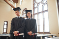 Two men in graduation gowns and caps indoors - PhotoDune Item for Sale