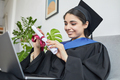 Smiling young woman videochatting at graduation - PhotoDune Item for Sale