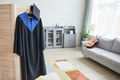 Graduation gown on hanger at home - PhotoDune Item for Sale