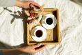 Breakfast in bed, female hands put try with two cups coffee and flower in sunlight - PhotoDune Item for Sale