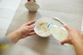 Female hand holding bottle pouring milk in cereal granola flakes bowl - PhotoDune Item for Sale