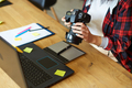 Photographer female working in a creative office holding camera, at desk and retouch photo - PhotoDune Item for Sale