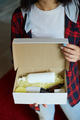 Brunette woman opening, hold in hand online order parcel box with cosmetics at home - PhotoDune Item for Sale