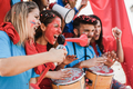 Crazy sport fans playing drums and screaming while supporting their team - Focus on left woman face - PhotoDune Item for Sale