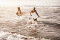 Father and son running on the beach at sunset for surf training - Focus on right man - PhotoDune Item for Sale