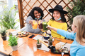 Happy multiracial friends cheering with juice at restaurant outdoors with mask under chins - PhotoDune Item for Sale