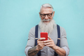 Happy senior hipster man using mobile phone outdoors in the city - Focus on face - PhotoDune Item for Sale