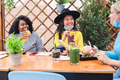Happy multiracial friends having fun at restaurant outdoors with masks under chins - PhotoDune Item for Sale