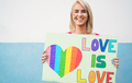 Portrait of gay woman holding love is love banner at lgbt pride parade - Focus on face - PhotoDune Item for Sale