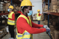 African warehouse worker loading delivery boxes while wearing safety mask - Focus on face - PhotoDune Item for Sale