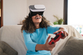 Girl with afro hair playing console games wearing virtual reality goggles at home - PhotoDune Item for Sale