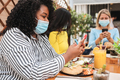 Multiracial girls using mobile phone app sitting at restaurant - PhotoDune Item for Sale