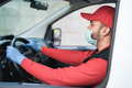 Delivery man driving truck van whil wearing face mask during coronavirus outbreak - Focus on face - PhotoDune Item for Sale