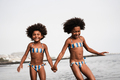 Happy african sister twins running on the beach together - Main focus on right girl - PhotoDune Item for Sale