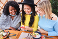 Happy multiracial friends using mobile phone outdoors at brunch restaurant with mask under chins - PhotoDune Item for Sale