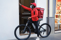 African delivery man with electric bike ringing the doorbell - Focus on face - PhotoDune Item for Sale