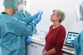 Doctor measuring fever to senior woman before coronavirus vaccination - Focus on patient - PhotoDune Item for Sale