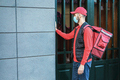 Young delivery man with thermal backpack ringing the doorbell during coronavirus lockdown - PhotoDune Item for Sale