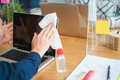 Young worker using antiseptic gel to disinfect screen laptop computer inside modern office - PhotoDune Item for Sale
