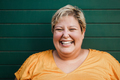 Portrait of curvy woman smiling on camera outdoors with green background - Focus on face - PhotoDune Item for Sale
