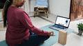 African senior woman doing online yoga lesson at home during coronavirus outbreak - PhotoDune Item for Sale