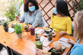 Young multiracial people talking in restaurant outdoors while wearing safety masks - PhotoDune Item for Sale