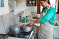 Hispanic mature woman cooking dinner inside vintage kitchen at home - Focus on right hand - PhotoDune Item for Sale