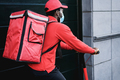African rider delivering meal with electric scooter - Focus on backpack - PhotoDune Item for Sale