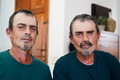 Portrait of senior twin men smiling on camera indoors at home - Focus on faces - PhotoDune Item for Sale