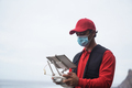 Courier man flying box for delivery with drone while wearing safety mask - Focus on face - PhotoDune Item for Sale