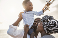 African parents and little son having fun with wood airplane on the beach - PhotoDune Item for Sale