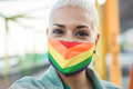 Close up of proud happy young lesbian woman holding lgbt rainbow flag - Focus on face - PhotoDune Item for Sale