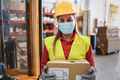 Portrait of worker woman holding cardboard box inside warehouse while wearing safety mask - PhotoDune Item for Sale