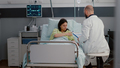 Caucasian female with nasal oxygen tube sitting in bed in hospital ward - PhotoDune Item for Sale
