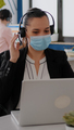 Close up of businesswoman with face mask wearing headset talking into microphone - PhotoDune Item for Sale