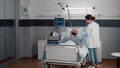 Sick man resting in bed while therapist doctor monitoring respiratory recovery - PhotoDune Item for Sale