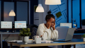 Overworked african manager woman massaging head while sitting at workplace - PhotoDune Item for Sale