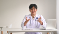 A young doctor in a medical uniform looks at the camera to provide health advice. - PhotoDune Item for Sale