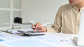A young man with a pen in hand is operating a calculator, graphing data and laptop on the desk. - PhotoDune Item for Sale