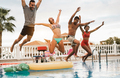 Multiracial friends having fun jumping inside pool during summer vacation - PhotoDune Item for Sale