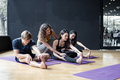 Group of young people doing yoga on a yoga mat with a trainer gradually teaching. - PhotoDune Item for Sale