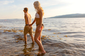Couple holding hands and wading in the sea in the evening - PhotoDune Item for Sale
