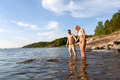 Man helping beautiful woman and holding hands when standing in the water - PhotoDune Item for Sale