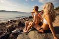 Young Couple Eating Flavored Ice On Rocks At Beach - PhotoDune Item for Sale