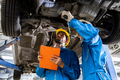 Two mechanic was checking the car suspension. - PhotoDune Item for Sale
