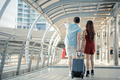 Young couple with dragging a suitcase and talking while to travel in the city. - PhotoDune Item for Sale