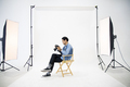 Young photographer man sitting wood chair and checking file on center white scene in studio. - PhotoDune Item for Sale