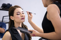Professional makeup artist working with beautiful young woman. - PhotoDune Item for Sale