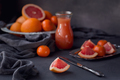 Glass of freshly squeezed grapefruit juice with fresh citrus fruits on dark background. - PhotoDune Item for Sale