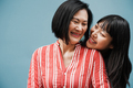 Asian mother and daughter hugging outdoors with blue background - Main focus on senior woman face - PhotoDune Item for Sale